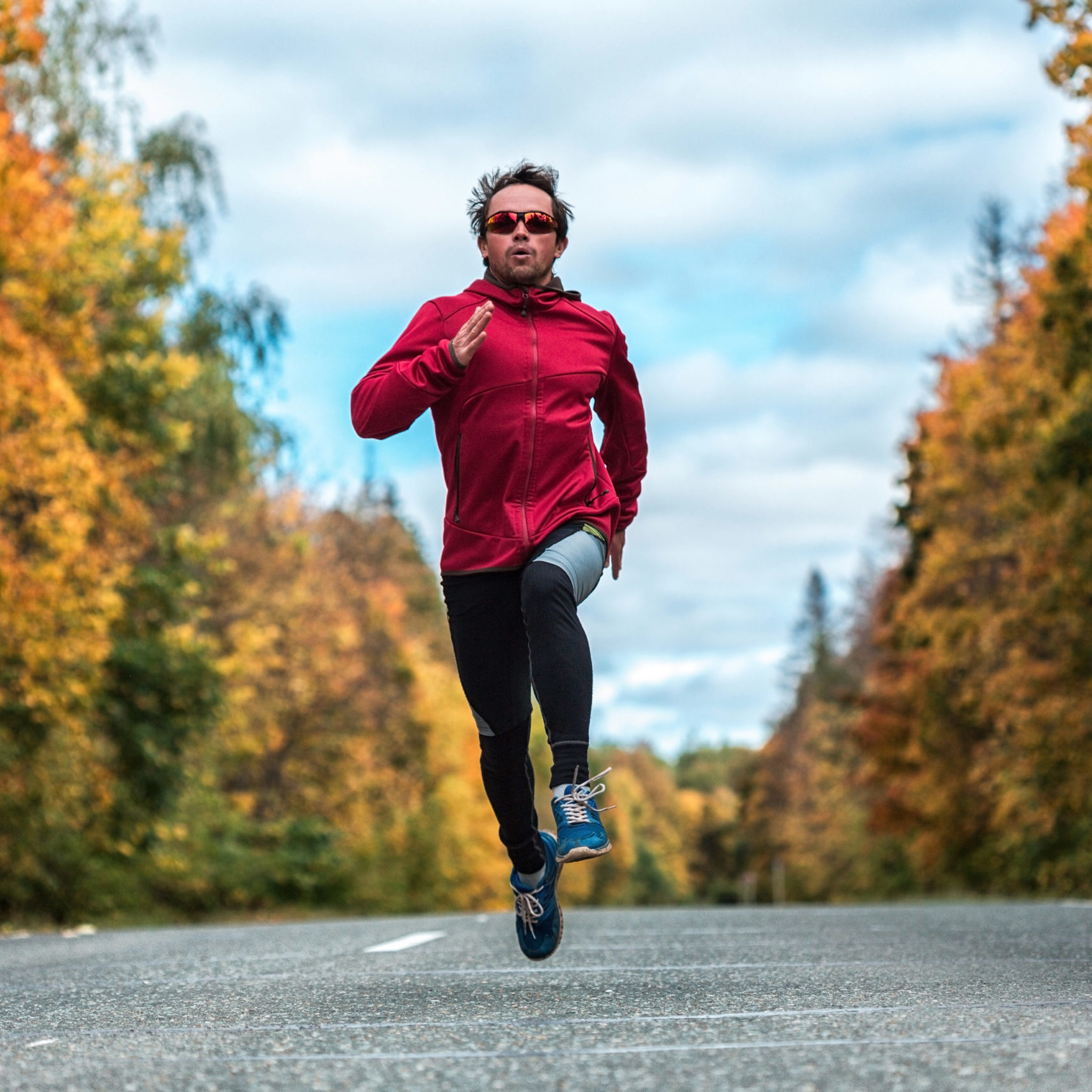 Young athlete running on the autumn road